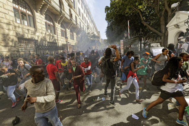 Protesting university students flee as police fire stun grenades outside Parliament in Cape Town, South Africa, Wednesday October 21, 2015. The protests are part of a wave of nationwide protests that have shut down many South Africa universities, which say they are struggling with higher operational costs as well as inadequate state subsidies. (Photo by AP Photo)