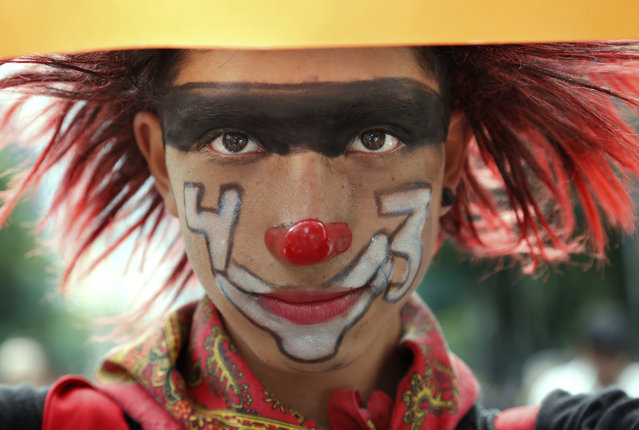 A demonstrator dressed as a clown and the number 43 painted on her face poses for a photo during a protest march in Mexico City, Monday, September 26, 2016. The march was held on the second anniversary of the disappearance, on September 26, 2014, of 43 students from the Rural Normal School at Ayotzinapa. The government's initial investigation decided the students were killed and incinerated in a fire. But international experts have cast doubt on this theory and the families have not accepted it. (Photo by Marco Ugarte/AP Photo)