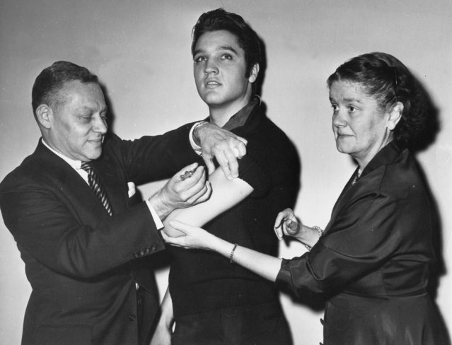 A shot in the arm - Elvis Presley receives a salk polio vaccine shot in New York City on October 28. Giving the shot is Dr. Harold Fuerst of New York. Holding Presleys arm is Dr. Leona Baumgartner, commissioner of the New York City health department. Presley is known for his gyrations while presenting a song. (Photo by AP Photo)
