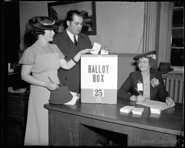 """Washington Votes; first time since 1874. Washington, D.C., April 30. It was a long time between votes, 1874 to 1938, but the Capitol bridged a gap today when its residents cast a city-wide ballot on the question of whether suffrage shall be voted to the voteless community. Mr and Mrs Paul R. Henry are shown depositing their ballots while Miss Magdalena Gale registers them, 4/30/38"". Photographed by Harris & Ewing."
