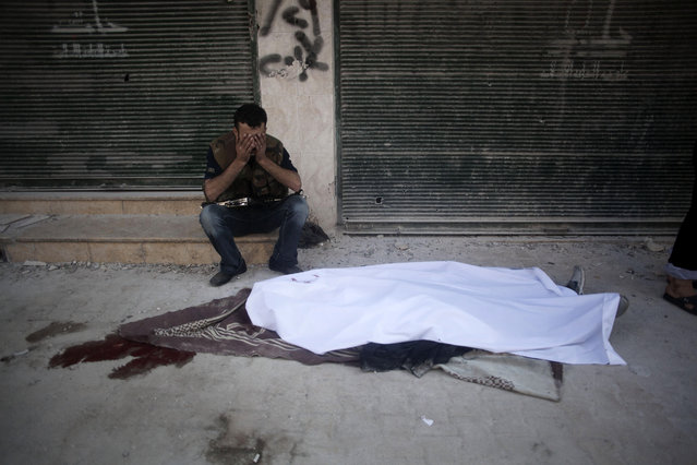 A Free Syrian Army fighter cries near the body of his comrade in front of Dar El Shifa hospital in Aleppo, Syria, Tuesday, September 25, 2012. (Photo by Manu Brabo/AP Photo)