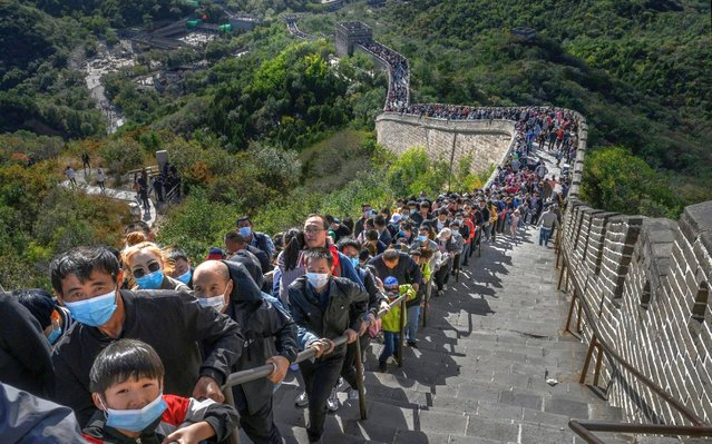 """Chinese tourists line up at a bottleneck as they climb a section of the Great Wall at Badaling after tickets sold out during the """"Golden Week"""" holiday on October 4, 2020 in Beijing, China. Officials are expecting the Golden Week holiday to boost China's consumer economy as people were encouraged to use the 8-day break to travel and spend. Tourist sites including the Great Wall were packed, with tickets selling out most days given pandemic restrictions and capacity capped at 75%. (Photo by Kevin Frayer/Getty Images)"""