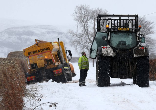 A gritting vehicle waits to be pulled from a ditch near Kippen in Stirlingshire, UK after snowfall on March 22, 2013. (Photo by Andrew Milligan/PA Wire)