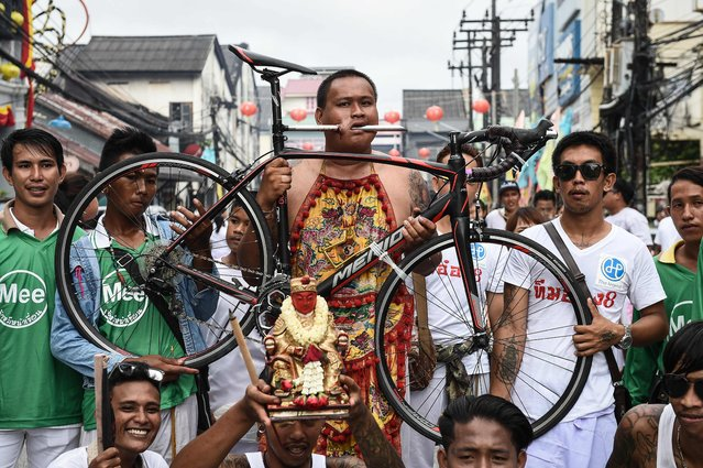 A devotee of the Nine Emperor Gods parades through the town of Phuket with a bicycle attached to his cheek during the annual Phuket Vegetarian Festival in the southern province of Phuket on October 3, 2016. Southern Thailand's gruesome vegetarian festival got under way on October 2 and devotees throughout the week will show their religious devotion through ritualistic self-mutilation and pain trials, including running over hot coals and piercing their bodies with an astonishing – and stomach-turning – variety of objects. (Photo by Lillian Suwanrumpha/AFP Photo)