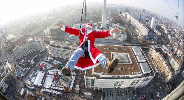 A man dressed as Santa Claus poses during a base flying event in downtown in Berlin December 6, 2014. Participants of the event hosted by entertainment agency Jochen Schweizer flew down 98 metres (322 ft.) from atop the hotel in the German capital. (Photo by Hannibal Hanschke/Reuters)