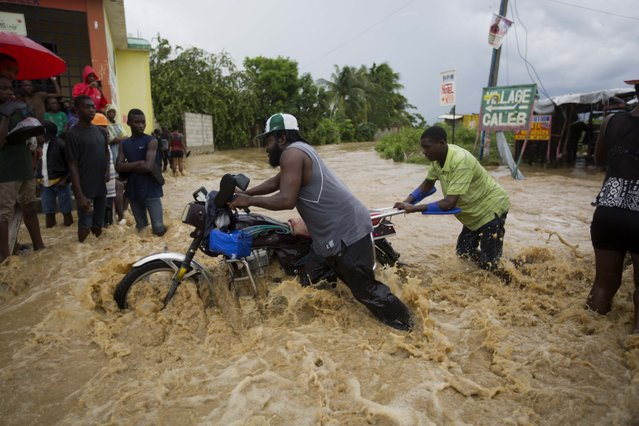 Men push a motorbike through a street flooded by a river that overflowed from heavy rains caused by Hurricane Matthew in Leogane, Haiti, Wednesday, October 5, 2016. Rescue workers in Haiti struggled to reach cutoff towns and learn the full extent of the death and destruction caused by Hurricane Matthew as the storm began battering the Bahamas on Wednesday and triggered large-scale evacuations along the U.S. East Coast. (Photo by Dieu Nalio Chery/AP Photo)