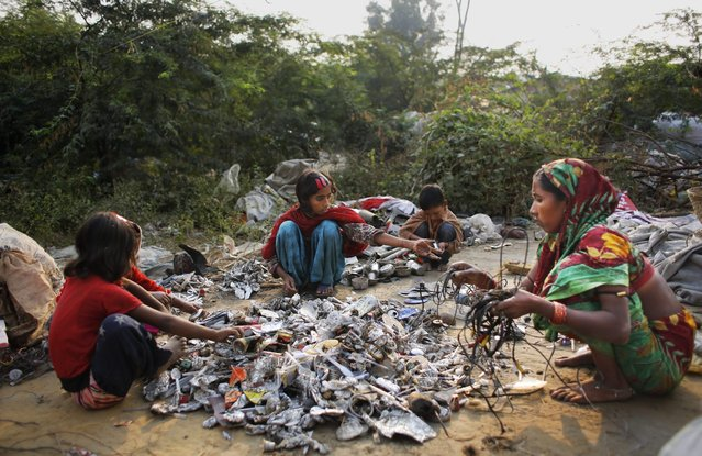 In this November 11, 2014 photo, Marjina, right, segregates trash with the help of her children and a young neighbor outside their rented shanty on the outskirts of New Delhi, India. (Photo by Altaf Qadri/AP Photo)