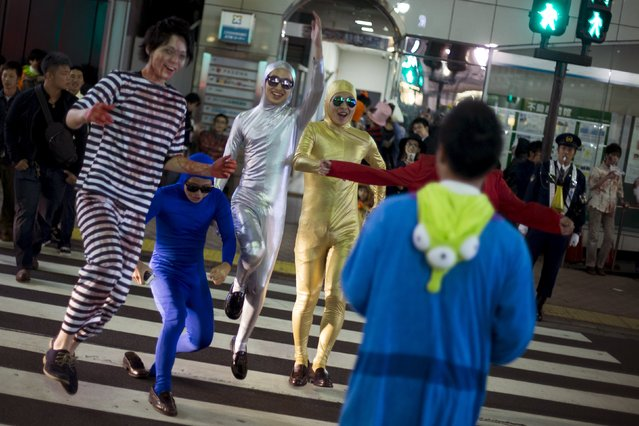 People dressed up in costumes greet a friend as they cross a street during Halloween celebrations in the Shibuya district of Tokyo, Japan October 31, 2015. (Photo by Thomas Peter/Reuters)