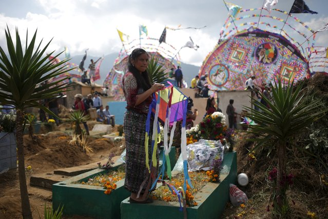 A woman holds a kite over a grave in the cemetery of Santiago Sacatepequez, Guatemala, November 1, 2015. (Photo by Jorge Dan Lopez/Reuters)