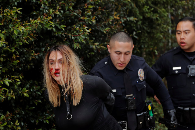 A woman with a bloody nose is detained after a scuffle by police officers outside of the Roosevelt Hotel in Hollywood, Los Angeles, California, U.S., March 3, 2018. (Photo by Lucas Jackson/Reuters)