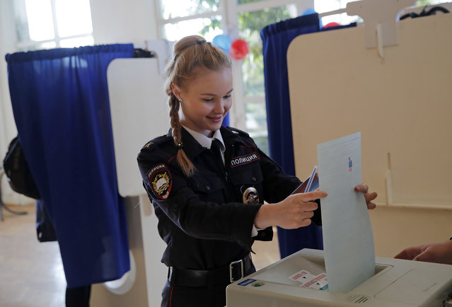 A police cadet casts her vote in the presidential election in Moscow, Russia, Sunday, March 18, 2018. Vladimir Putin headed to an overwhelming win in Russia' s presidential election Sunday, adding six years in the Kremlin for the man who has led the world' s largest country for all of the 21 st century. (Photo by Pavel Golovkin/AP Photo)