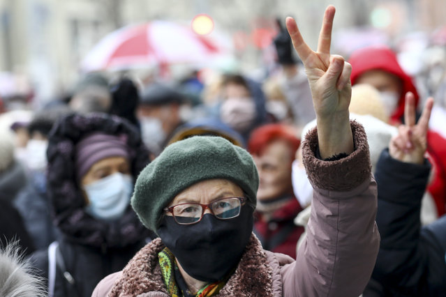 A woman wearing a face mask to protect against coronavirus gestures as she attends a pensioners' opposition rally to protest the official presidential election results in Minsk, Belarus, Monday, November 16, 2020. Crowds of retirees marched down the streets of the Belarusian capital on Monday, demanding the resignation of the country's authoritarian president and to end the government crackdown on peaceful protesters. (Photo by AP Photo/Stringer)