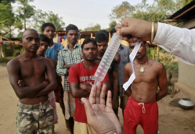 A volunteer from a non-governmental organisation (NGO) demonstrates how to use a condom to villagers during an AIDS awareness campaign on the outskirts of Agartala, India, November 6, 2015. India provides free condoms under its community-based AIDS prevention programme that targets high-risk groups like s*x workers. That strategy, the World Bank estimates, helped avert 3 million HIV infections between 1995 and 2015. (Photo by Jayanta Dey/Reuters)