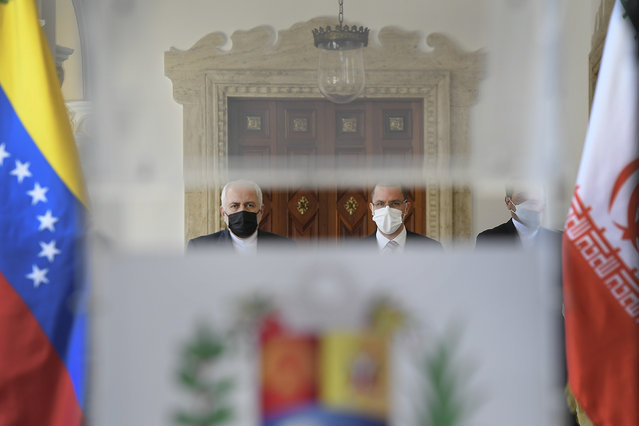 Seen through a translucent podium, Iran's Foreign Minister Mohammad Javad Zarif, left, and Venezuela's Foreign Minister Jorge Arreaza, right, arrive to give a press conference at the Foreign Ministry in Caracas, Venezuela, Thursday, November 5, 2020, amid the COVID-19 pandemic. (Photo by Matias Delacroix/AP Photo)