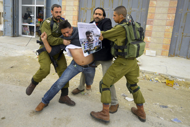 In this Friday, December 12, 2014 photo, Israeli soldiers grab a Palestinian holding a poster showing late Cabinet minister Ziad Abu Ain during a protest in Bethlehem, West Bank. Abu Ain  collapsed and died shortly after scuffling with Israeli troops during a West Bank protest Wednesday. (Photo by Mahmoud Illean/AP Photo)