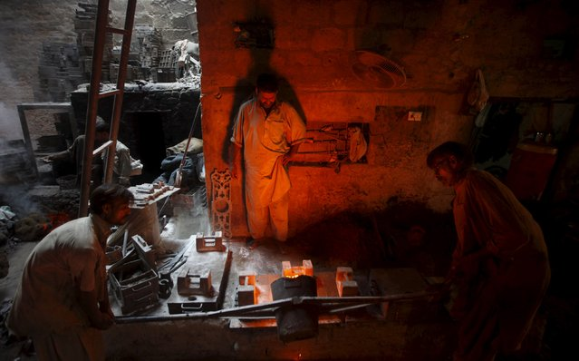 Workers pour molten iron into a mould as they make parts for textile machinery at a factory in Karachi, Pakistan October 17, 2015. (Photo by Athar Hussain/Reuters)