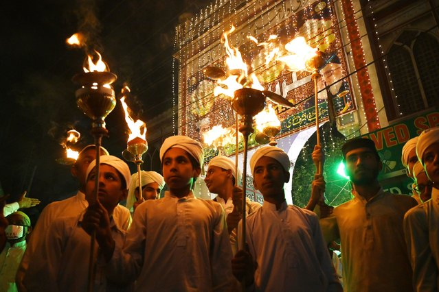 Muslims hold torch lights during a rally ahead of celebrations for Eid-e-Milad-un-Nabi, the birthday of Prophet Mohammad, in Lahore on October 29, 2020. (Photo by Arif Ali/AFP Photo)