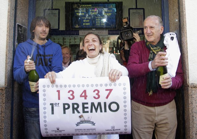 """Lottery seller Raquel Carrasco (C) holds a sign with the winning number of Spain's Christmas Lottery """"El Gordo"""", in La Eliana near Valencia December 22, 2014. (Photo by Heino Kalis/Reuters)"""