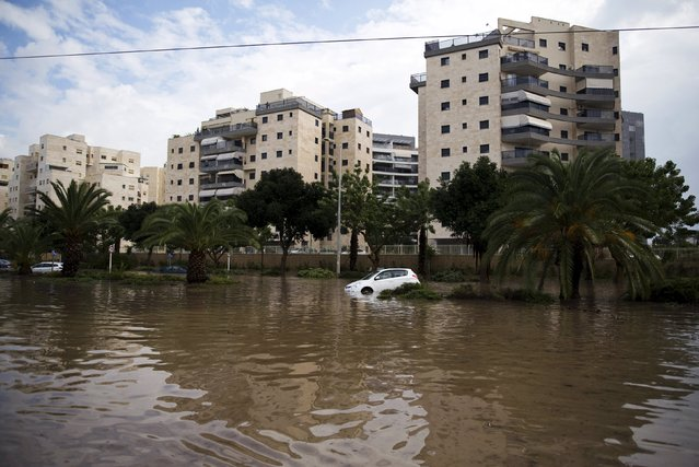 A parked vehicle is seen on a flooded street in the southern city of Ashkelon, Israel, November 9, 2015. (Photo by Amir Cohen/Reuters)