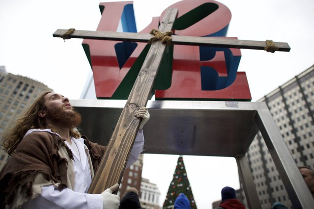 "Upon reaching LOVE Park in Center City, Michael Grant, 28, ""Philly Jesus"", lifts the 12 foot cross he had carried 8 miles through North Philadelphia as part of a Christmas walk to spread the true message of the holiday in Philadelphia, Pennsylvania December 20, 2014. (Photo by Mark Makela/Reuters)"
