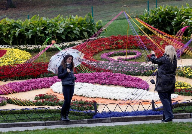 A woman with umbrella poses for a picture during a visit to a flower exhibition on a rainy autumn day in Kiev, Ukraine October 7, 2016. (Photo by Valentyn Ogirenko/Reuters)