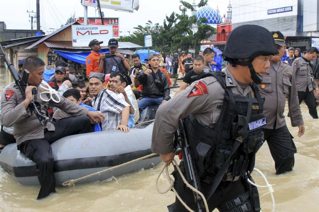Indonesian police guard prisoners who were evacuated from a local prison due to flooding in Lhoksukon, Aceh province December 23, 2014 in this photo taken by Antara Foto. A total of 200 prisoners were forced to evacuate after flood waters from heavy rains reached 2 meters high. (Photo by Reuters/Antara Foto/Rahmad)