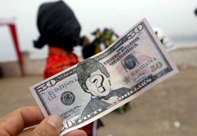 """Actors portraying """"corrupted people"""" participate in the """"Unmask the Corrupt"""" event, organized by the Transparency International non-governmental organization to create awareness on corruption, in Lima, November 12, 2015. (Photo by Mariana Bazo/Reuters)"""