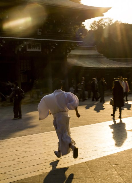 A Shinto priest runs across the yard during ceremonies bidding farewell to 2014, ahead of New Year's Day, at the Meiji Shrine in Tokyo December 31, 2014. (Photo by Thomas Peter/Reuters)