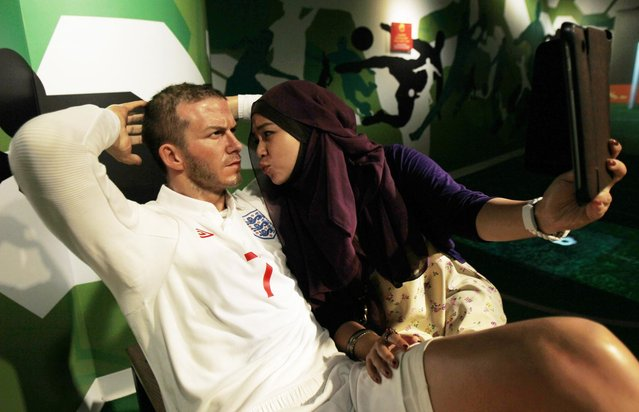 A woman poses with a wax figure of David Beckham at Madame Tussauds Wax Museum in Bangkok May 17, 2013. England's best known footballer David Beckham announced his retirement on Thursday after a career laden with trophies and glamour that had a worldwide impact that went way beyond soccer. (Photo by Chaiwat Subprasom/Reuters)