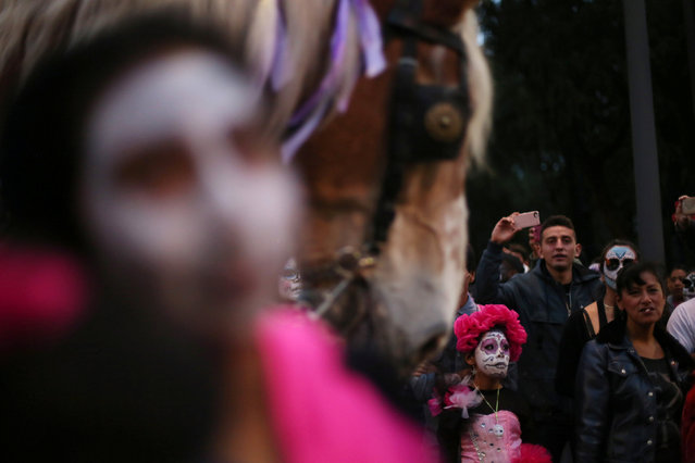 "People with their faces painted to look like the popular Mexican figure called ""Catrina"" take part in a procession to celebrate the upcoming annual Day of the Dead on November 1 and 2, at Reforma avenue, in Mexico City, Mexico, October 23, 2016. (Photo by Edgard Garrido/Reuters)"