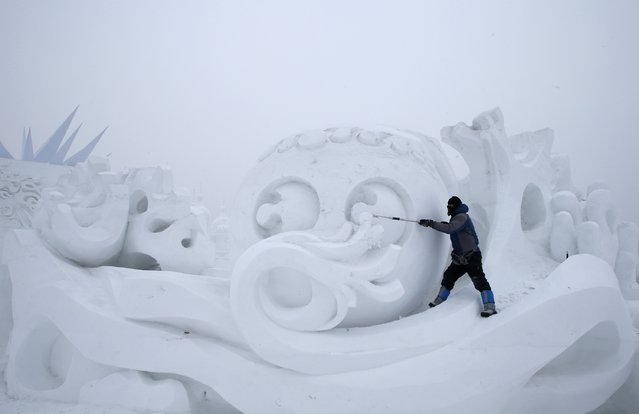 A worker polishes a snow sculpture ahead of the 31st Harbin International Ice and Snow Festival in the northern city of Harbin, Heilongjiang province, January 4, 2015. (Photo by Kim Kyung-Hoon/Reuters)