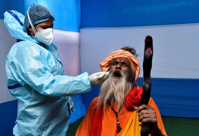"A Sadhu or a Hindu holy man reacts as a healthcare worker wearing personal protective equipment (PPE) collects a swab sample from him for a rapid antigen test at a base camp where pilgrims gather before heading for an annual trip to Sagar Island for the one-day festival of ""Makar Sankranti"", amidst the spread of the coronavirus disease (COVID-19) in Kolkata, India, January 8, 2021. (Photo by Ranita Roy/Reuters)"