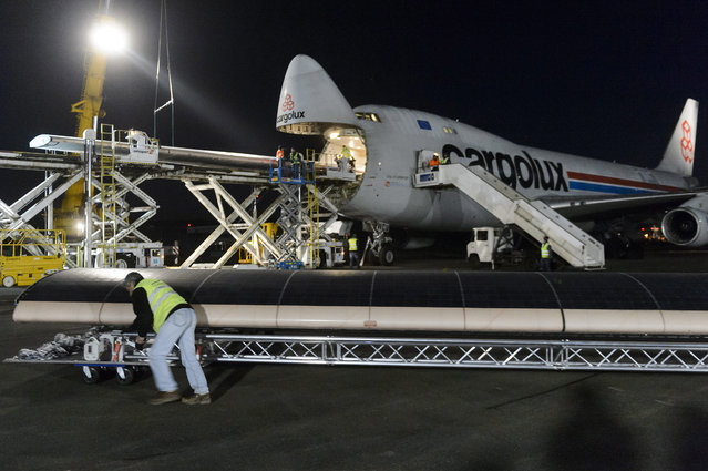 """Solar Impulse crew members load a piece of the wing of the experimental aircraft """"Solar Impulse 2"""" (HB-SIB) into a Boeing 747 cargo plane at the airbase in Payerne, Switzerland, 05 January 2015. A Boeing 747 plane will take off early 06 January carrying the experimental aircraft Solar Impulse to Abu Dhabi in the United Arab Emirates. (Photo by Laurent Gillieron/EPA)"""