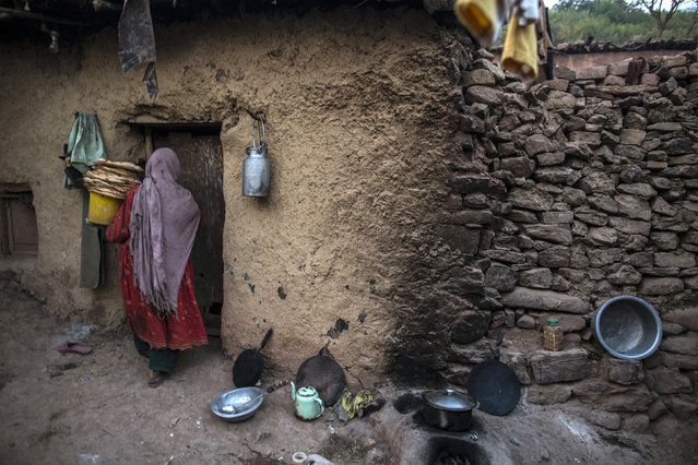 A woman, whose family moved to Islamabad from Pakistan's Khyber-Pakhtunkhwa province to look for work, carries a pile of bread as she enters her house on the outskirts of Islamabad January 1, 2015. (Photo by Zohra Bensemra/Reuters)