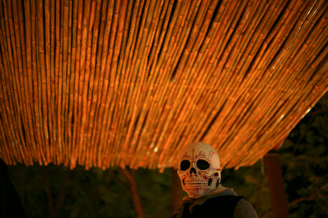 A man wearing a skull mask is pictured on the Day of the Dead at  Santa Maria Atzompa cemetery in Oaxaca Mexico, November 1, 2016. (Photo by Jorge Luis Plata/Reuters)