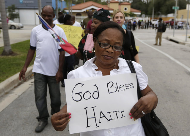 Marilia Lexsidor walks during a silent march commemorating the fifth anniversary of a devastating earthquake that struck Haiti, Monday, January 12, 2015, in the Little Haiti neighborhood of Miami. The 7.0 magnitude earthquake struck in 2010, and the Haitian government has said more than 300,000 people were killed. (Photo by Lynne Sladky/AP Photo)