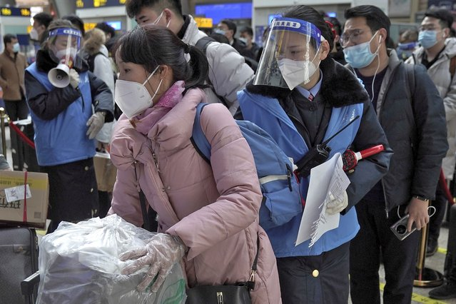 Workers wearing face masks and face shields to help curb the spread of the coronavirus assist masked passengers to board their trains at the South Train Station in Beijing, Thursday, January 28, 2021. (Photo by Andy Wong/AP Photo)