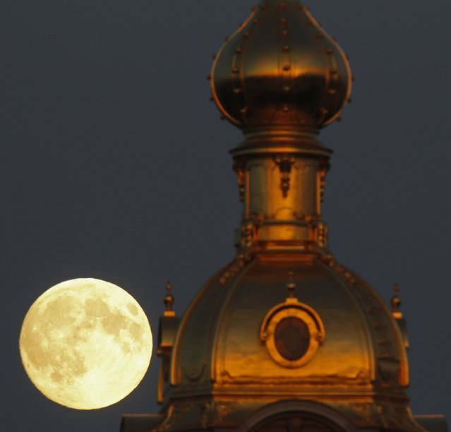 The moon rises behind the Peter and Pawel Fortress in St. Petersburg June 22, 2013. (Photo by Alexander Demianchuk/Reuters)