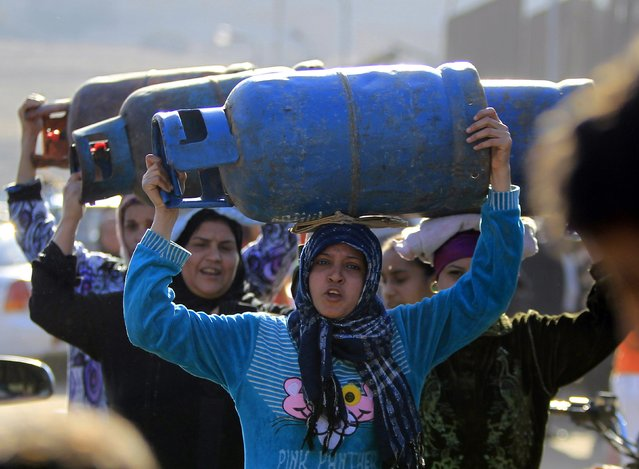 Women carry gas cylinders to fill them at a distribution point in Cairo January 19, 2015. Egypt is going through its worst energy crisis in decades and is seeking fresh sources of natural gas, which powers most of its homes and factories. (Photo by Mohamed Abd El Ghany/Reuters)