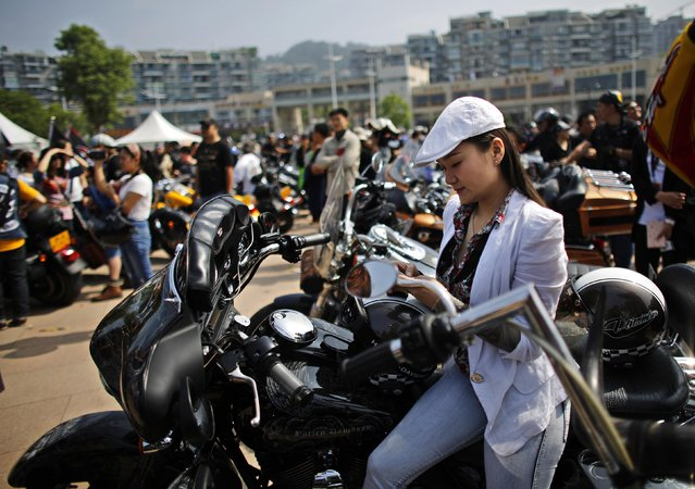 A woman sits on a Harley Davidson motorcycle during the annual Harley Davidson National Rally in Qian Dao Lake, in Zhejiang Province in this May 11, 2013 file photo. (Photo by Carlos Barria/Reuters)