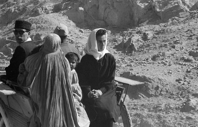 Afghan women, men, and child in traditional dress ride in a cart through an arid, rocky landscape, November, 1959. (Photo by Robert P. Martin/LOC via The Atlantic)