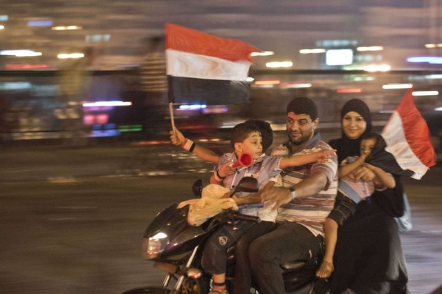 An Egyptian family on motorcycle celebrates in Cairo, on July 4, 2013. (Photo by Khaled Desouki/AFP Photo)