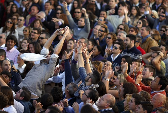 A man catches a packet of biscuits thrown from a balcony during the annual San Antonio Abad (Saint Anton Abbott) festival in Trigueros, southwest Spain January 25, 2015. (Photo by Marcelo del Pozo/Reuters)