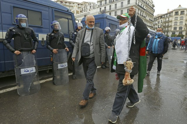 """A man holds a bone while shouting """"That's what's left for those who vote for the President"""" as Algerians demonstrate in Algiers to mark the second anniversary of the Hirak movement, Monday February 22, 2021. February 22 marks the second anniversary of Hirak, the popular movement that led to the fall of Algerian President Abdelaziz Bouteflika. (Photo by Anis Belghoul/AP Photo)"""