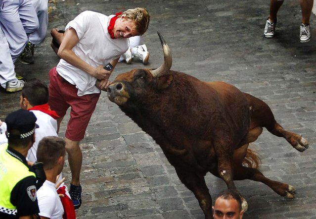 A runner is gored by an El Pilar fighting bull during the running of the bulls at the San Fermin festival in Pamplona, on July 12, 2013. An American and two Spaniards were gored Friday during a danger-filled sixth bull run, with one loose bull causing panic in the packed streets of the northern Spanish city. (Photo by Associated Press)