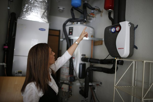 Computer science professor Christa Lopes points to a domestic hot water solar system in her home in Irvine, California January 26, 2015. (Photo by Lucy Nicholson/Reuters)