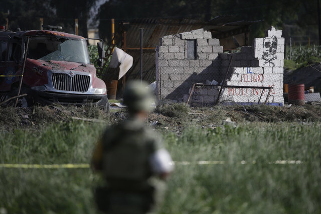 A soldier guards the perimeter around the wreckage of several fireworks workshops in Tultepec, Mexico, Thursday, July 5, 2018. More than a dozen people were killed and at least 40 injured when a series of explosions ripped through fireworks workshops in a town just north of Mexico City. (Photo by Moises Castillo/AP Photo)