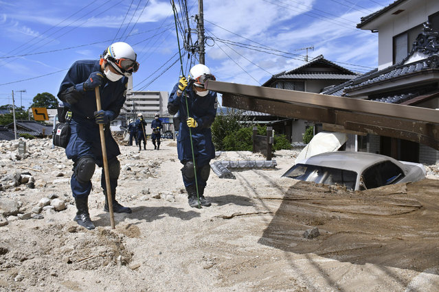 Police use sticks during a search operation at a mud-covered area in the aftermath of heavy rains in Kure, Hiroshima prefecture, southwestern Japan, Wednesday, July 11, 2018. Rescuers were combing through mud-covered hillsides and along riverbanks Tuesday searching for dozens of people missing after heavy rains unleashed flooding and mudslides in southwestern Japan. (Photo by Shingo Nishizume/Kyodo News via AP Photo)