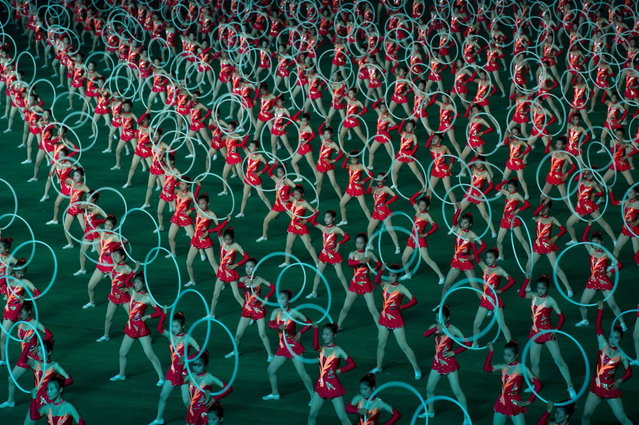 "Dancers use hoops during an ""Arrirang"" performance at the 150,000-seat Rungnado May Day Stadium in Pyongyang on July 26, 2013. Arrirang performances feature some 100,000 participants to create a ""synchronized socialist-realist spectacular in a 90 minute display of gymnastics, dance, acrobatics, and dramatic performance, in a highly politicized package"" according to the China-based North Korean travel company Koryo Tours. North Korea is preparing to mark the 60th anniversary of the end of the Korean War which ran from 1950 to 1953, with a series of performances, festivals, and cultural events culminating with a large military parade. (Photo by Ed Jones/AFP Photo)"