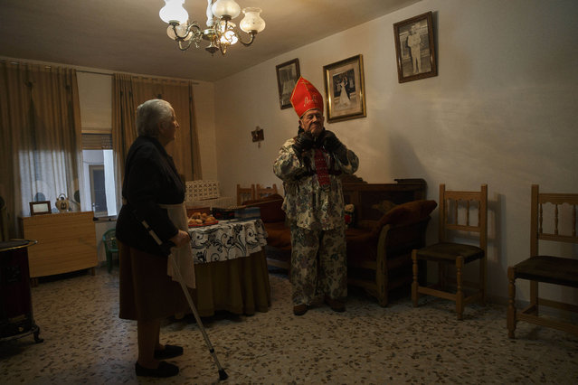 """Aniceto Rodrigo, 78, Diablo Mayor or """"greater devil"""", adjusts his mitre inside his home before walking around the village during the """"Endiablada"""" traditional festival in Almonacid Del Marquesado, Spain, Tuesday, February 3, 2015. The """"Endiablada"""" (The Brotherhood of the Devils) festivals are celebrated each Feb. 2-3 in the central Spanish town of Almonacid del Marquesado since medieval times or before. (Photo by Daniel Ochoa de Olza/AP Photo)"""